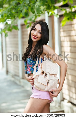 beautiful girl poses for the camera in the city on the street