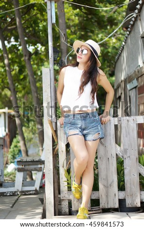 Beautiful girl posing in a summer park a bright sunny afternoon, fashion style, glamorous life, brunette in shorts and a T-shirt sneakers