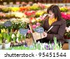Beautiful girl selecting flowers at market - stock photo