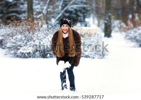 Beautiful girl smile fur gloves throwing snow to play and happy as child.