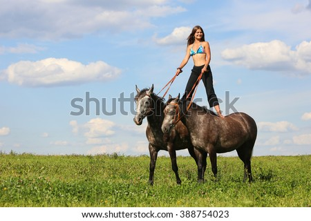 Beautiful girl standing on two horses