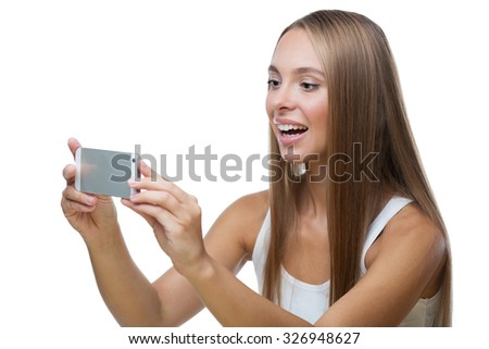 Beautiful girl taking pictures of something on the phone, looks at the screen and smiles, on the white background