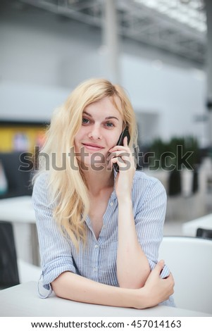 beautiful girl talking on the phone sitting in a shopping center, business center