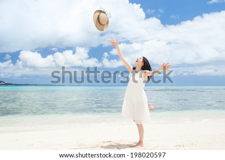beautiful girl throwing straw hat on the tropical island beach