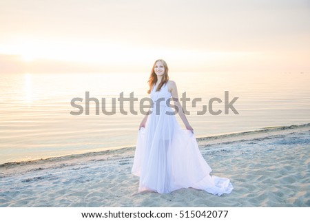 Beautiful girl walking on the beach in front of the stunning sunset.