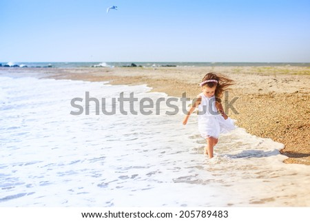 beautiful girl walks on the beach. happiness, holiday, wind, waves
