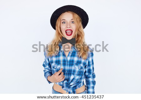 Beautiful girl wearing a hat and holding paper bow tie isolated on white. Excited blond teenage woman with bright makeup and red lips wearing blue shirt