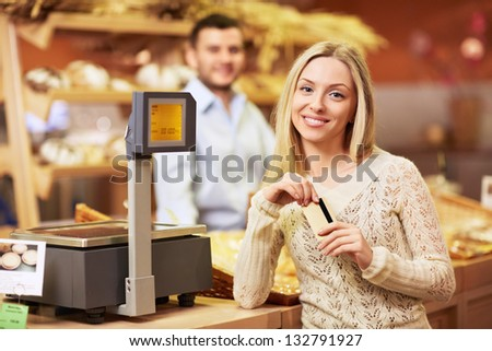 Beautiful girl with a credit card in a store