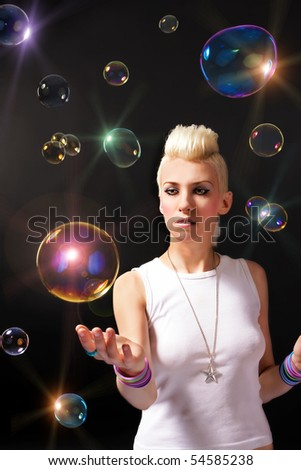 Beautiful girl with blonde hair and soap bubbles