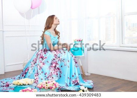 Beautiful girl with boxes of flowers in a bright interior