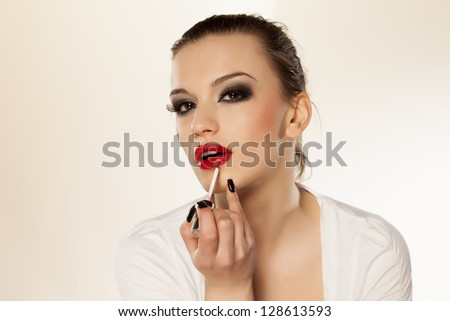 beautiful girl with bright makeup puts lip gloss