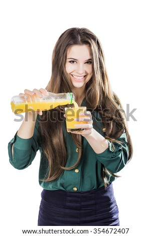 beautiful girl with dark hair pouring from a bottle into a glass of orange juice on a white background.