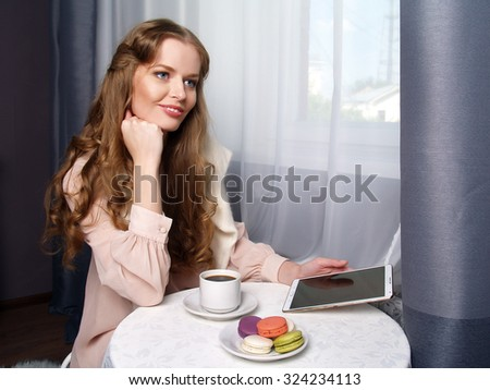 Beautiful girl with long hair is sitting in the cafe and smiling