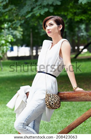 Beautiful girl with short red hair, dressed in white, resting in the middle of the park.