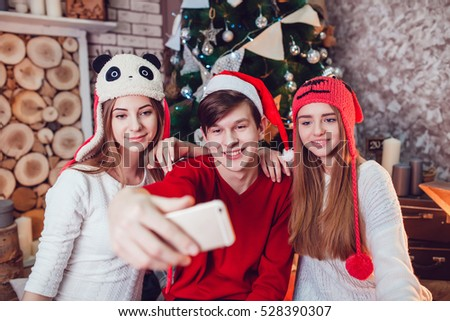 Beautiful girls and boy in funny hats sitting on the floor near a Christmas tree with gifts. Make selfie. New Year.