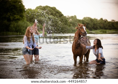 Beautiful girls and ponies swim in the river