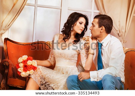 Beautiful glamour young couple is sitting on sofa and kissing at their dating.