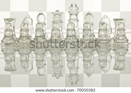 Beautiful glass chess on a white background. Photo taken in the studio on a glass countertop. Checkerboard is the background image.