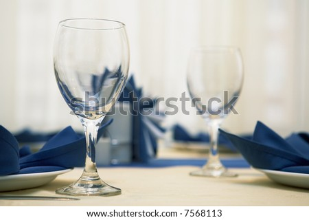 Beautiful glasses and dark blue napkins at fashionable restaurant