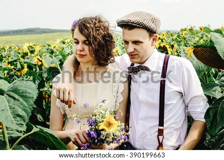 beautiful gorgeous bride and stylish handsome groom, rustic couple hugging in a sunflower sunny field