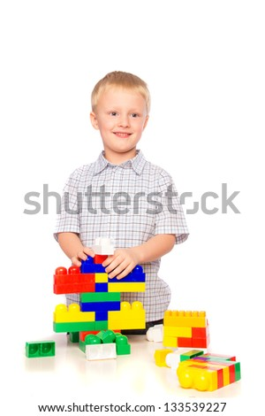Beautiful happy smiling joyful child (little boy) playing and  building plastic construction (educational game)  isolated on white background.