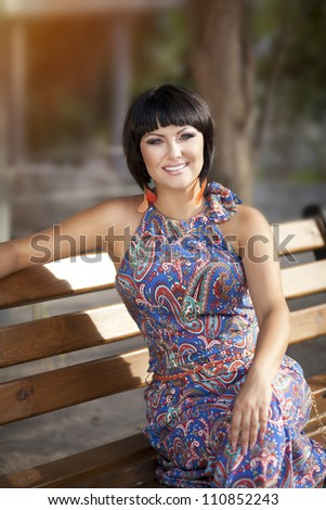 beautiful happy woman brunette sitting on bench in colorfull dress in park . young alluring girl smiling and resting on nature in sunny day. Autumn girl portrait.lady relaxing outdoors looking happy