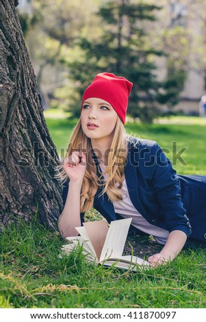 Beautiful happy young student girl in red hat holding book stands with backpack on green grass under the tree near the campus, university, school, education. Summer, spring green park