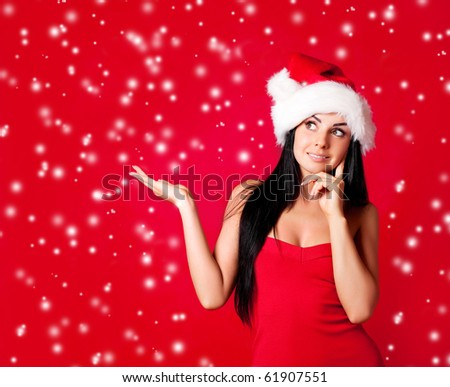 beautiful happy young woman dressed as santa with her hand up, place your product here