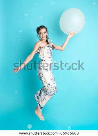 beautiful, happy, young woman jumping with an inflatable balloon in her hand, surrounded by soap balloons.