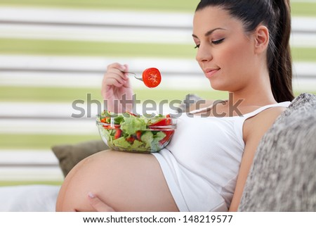 Beautiful healthy young pregnancy eating vegetable salad