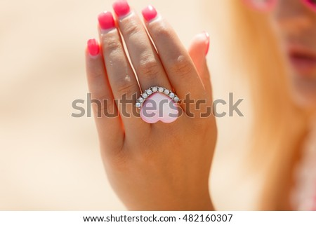 Beautiful heart ring on hand with diamonds. Propose in suny day outside. Love concept.