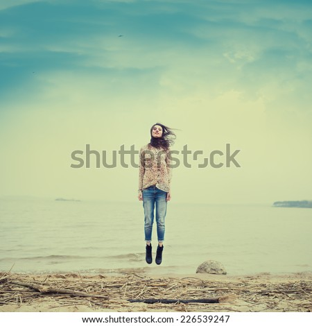 beautiful hipster girl flying on the beach