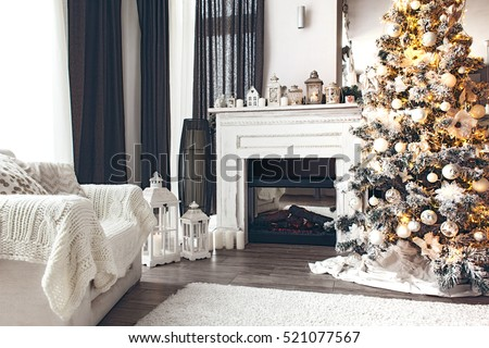 Beautiful holiday decorated room with Christmas tree, fireplace and armchair with blanket. Cozy winter scene. White interior with lights.