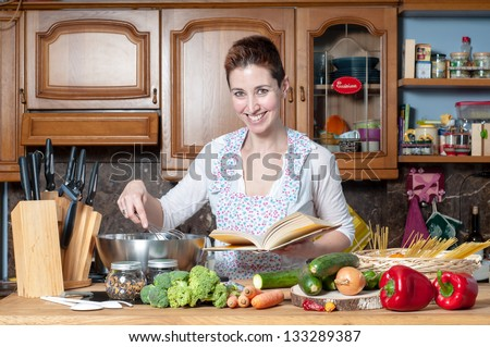 beautiful housewife cooking vegetables with cookbook in the kitchen