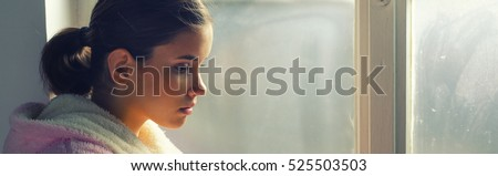 Beautiful ill sad girl in night gown looking through hospital window.