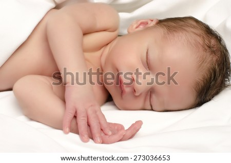 Beautiful innocent newborn sleeping. Adorable little boy relaxing in white sheets after a bath. Infant having sweet dreams