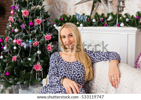 Beautiful lady sitting on sofa in room decorated for Christmas holidays