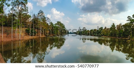 Beautiful lake nestled among rainforest in Cambodia under blue sky with white clouds. It surrounding mysterious ruins of Angkor Thom in Siem Reap, Cambodia