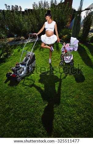 Beautiful laughing pregnant woman  with lawn mower and baby carriage near country house.
