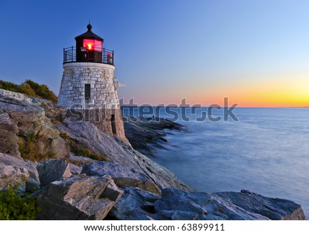 Beautiful lighthouse by the ocean at sunset