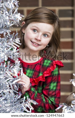Beautiful little girl beside silver Christmas tree wearing red and green pajamas.