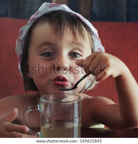 Beautiful little girl drinking from a cup