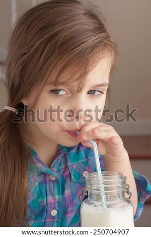 Beautiful little girl enjoying a glass of milk with a straw