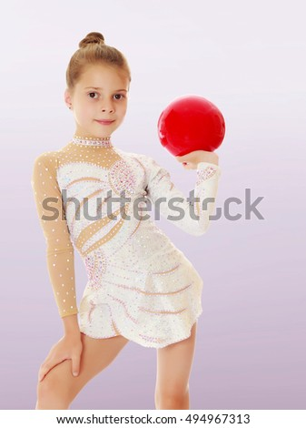Beautiful little girl gymnast in elegant dress, posing with a red ball.On a purple background.