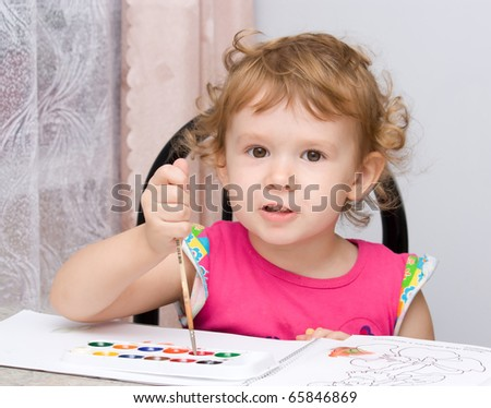 Beautiful little girl painting in album