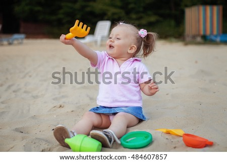 Beautiful little girl playing in the sandbox rake. The concept of childhood and development.