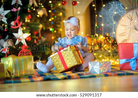 beautiful little girl, sits on a floor and considers Christmas gifts. Bright festive fires on a background. Waiting for a holiday.