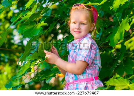 Beautiful little girl touches of green maple leaves and smiling