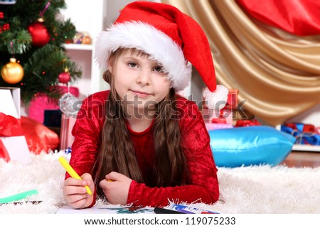 Beautiful little girl writes letter to Santa Claus in festively decorated room