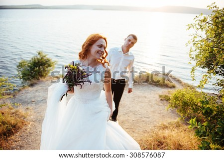 beautiful lovely blonde bride and groom classy on the rocks, amid the sea at sunset.